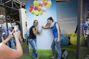 Una parte del materiale grafico creato. Due ragazze che fanno una foto fingendo di stringere dei palloncini, in realtà soltanto disegnati sulla parete dietro di loro
