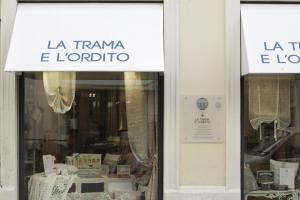 Oltre al Sito Iternet, 7emezzastudio ha realizzato anche tutti i materiali cartacei, in questa foto la cappottina e l'insegna del negozio. Sfondo bianco scritte blu